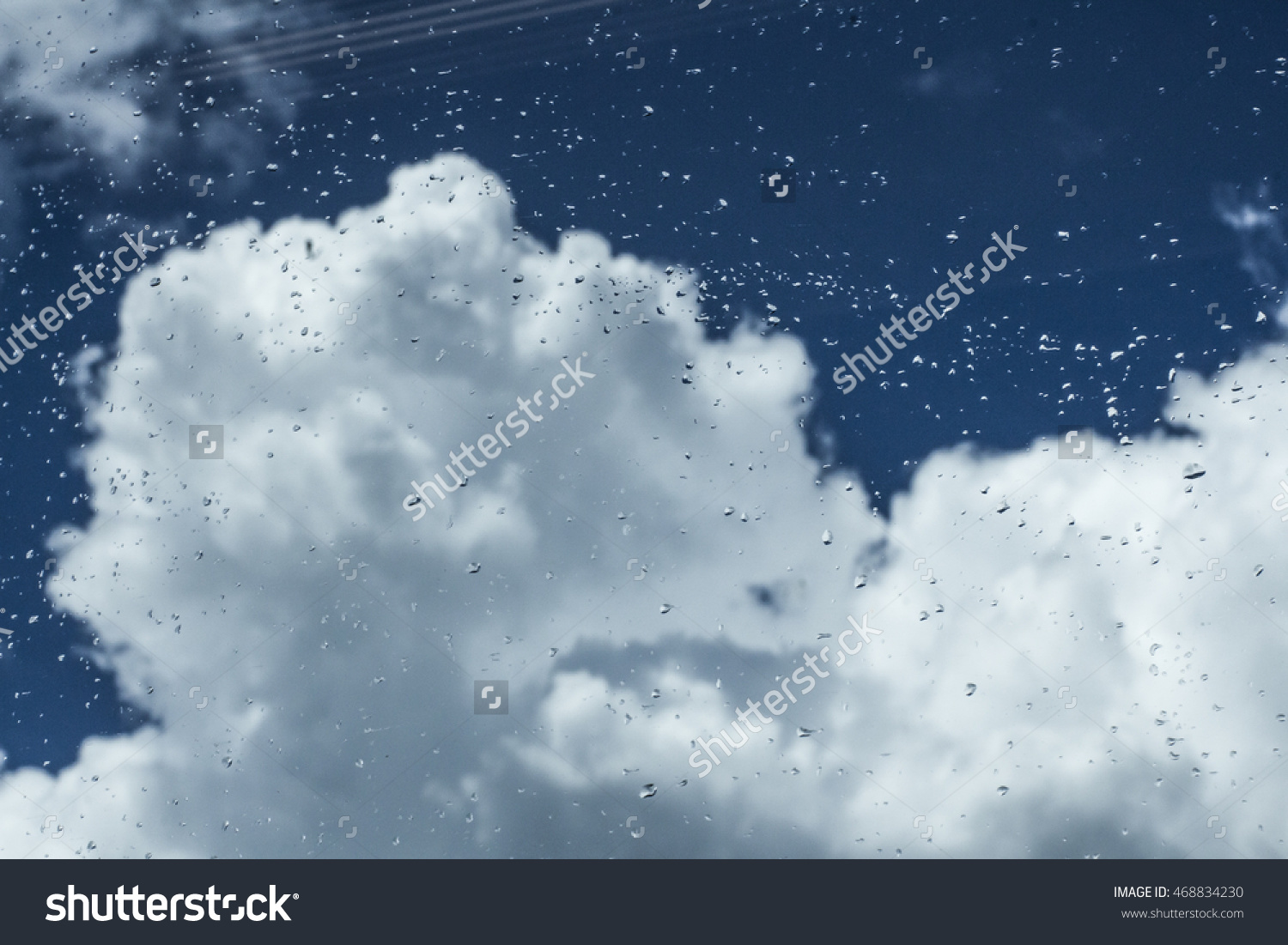 stock-photo-rainy-sky-with-white-clouds-and-raindrops-on-the-window-468834230